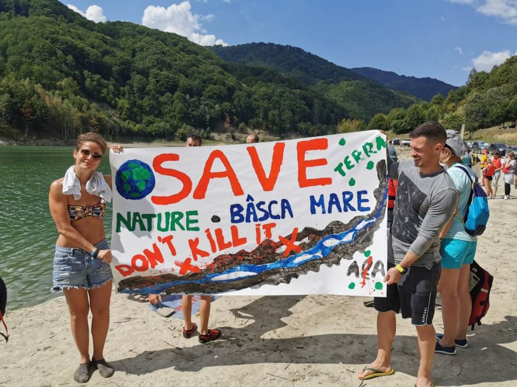 People holding banner with message to save nature
