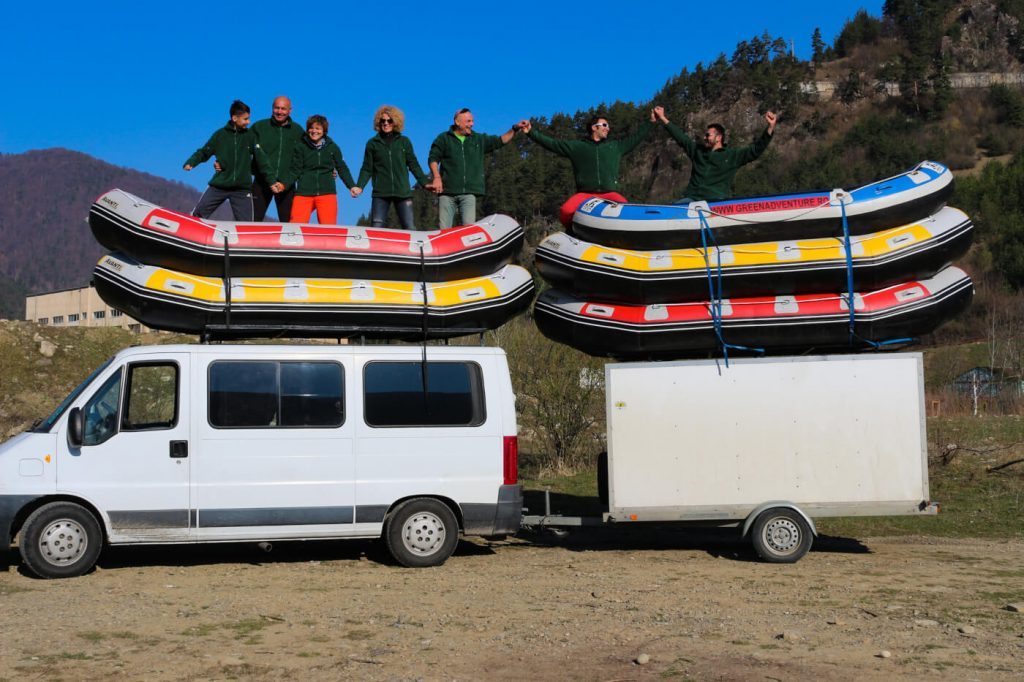 People holding hands on rafting boats on top of van