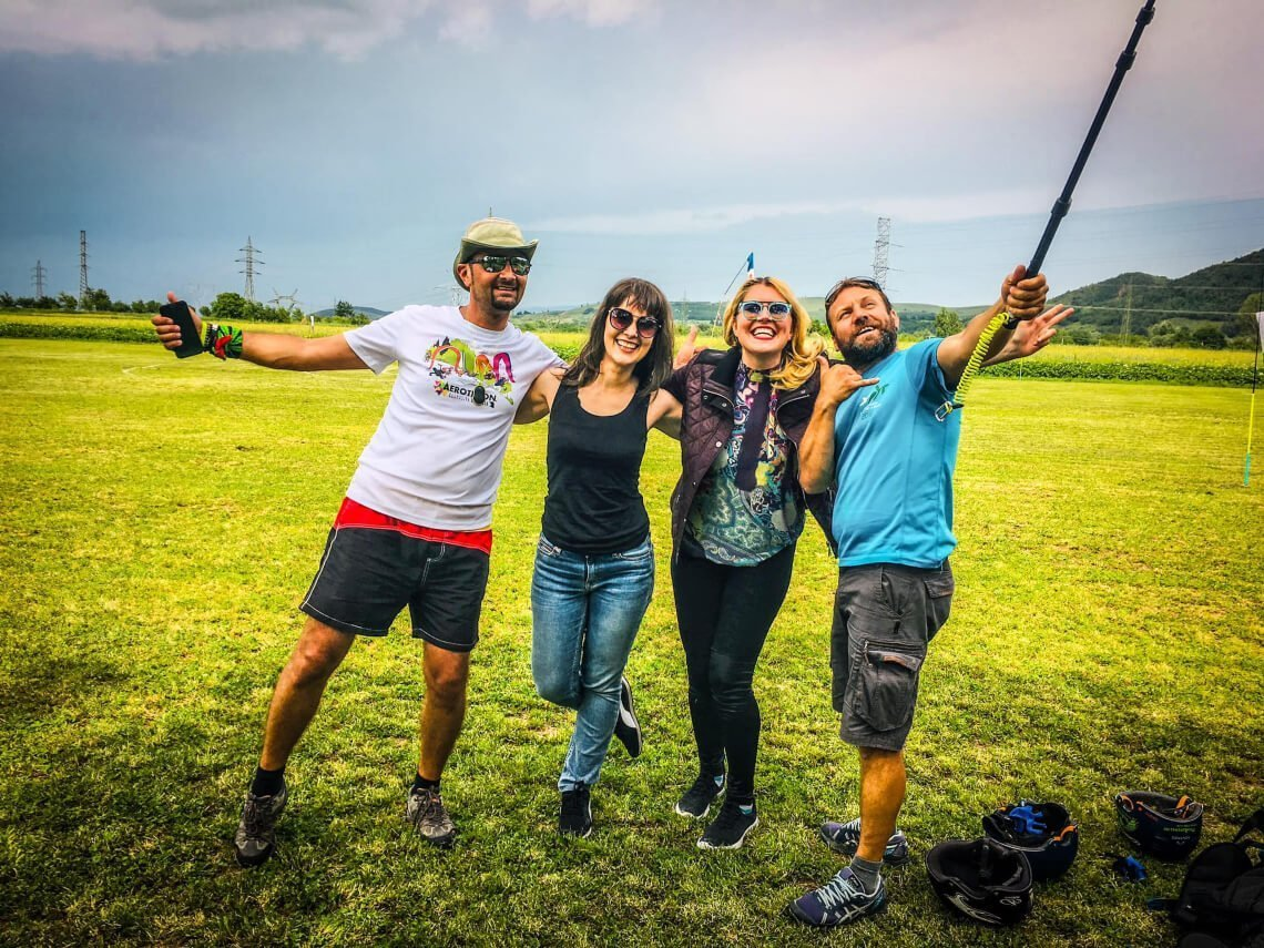 Friends and paragliding instructors on field after landing