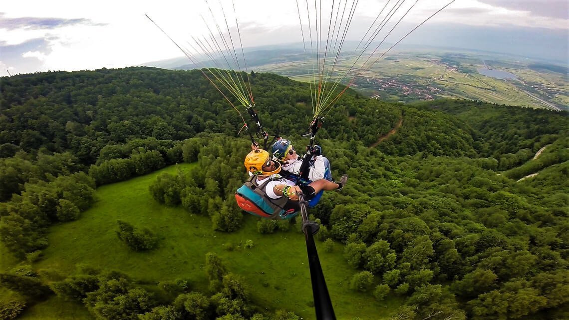 Tandem paragliding view over forest