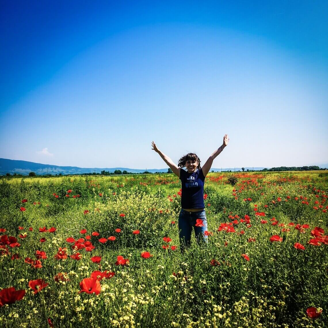 Girl jumping in a field of poppies